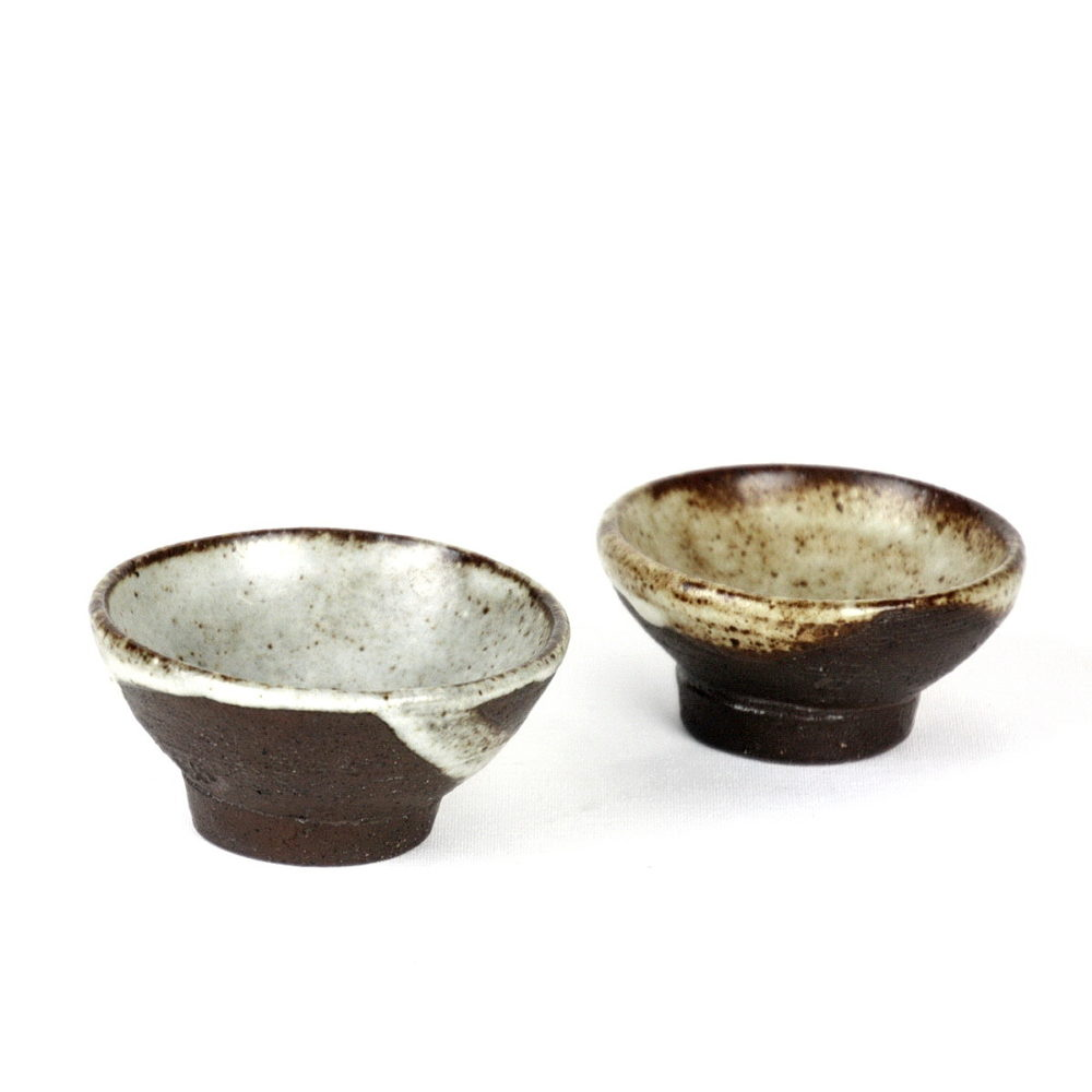 Janet Leach black clay sake cups with white glaze pours to interior and some to exterior. Part of set which included sake bottle