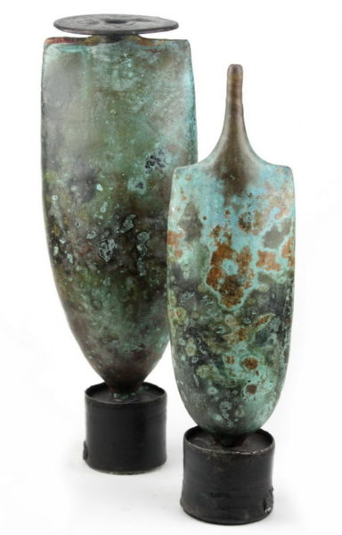 John Bedding eroded copper oxide earthenware vessels on pedestals. One with a torso shape and long neck the other with torso shape and large flat lip